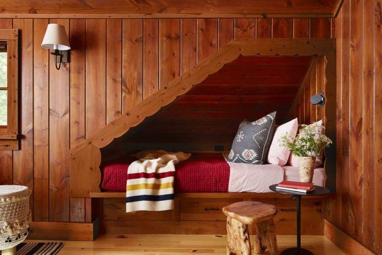 Une autre chambre entièrement recouverte de bois, avec des tabourets et des lampes confortables
