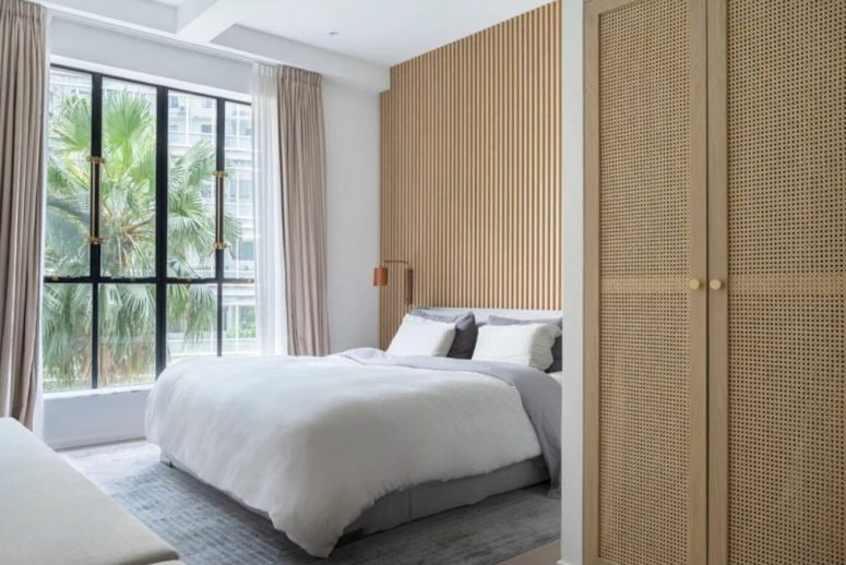 La chambre principale est faite avec un mur vitré, un mur en dalle de bois et des draps délicats