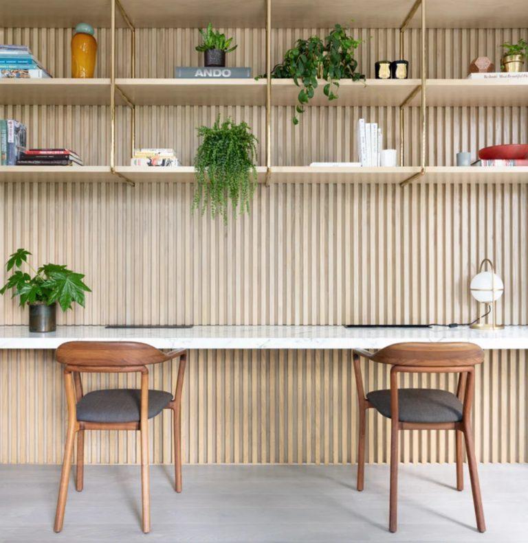 Le bureau à domicile est partagé, avec un bureau flottant, de nombreuses étagères suspendues et des chaises chics