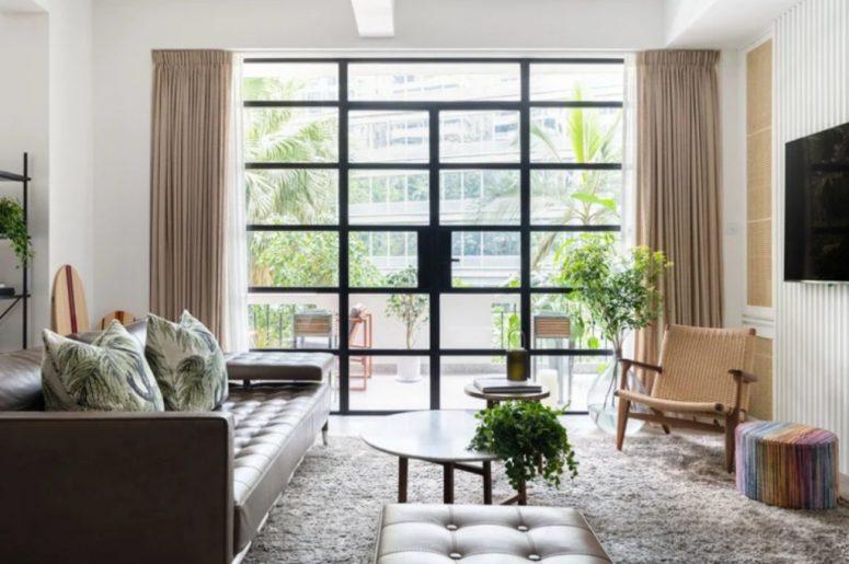 Le salon est fait avec un canapé en cuir et un pouf, avec une chaise tissée et un mur vitré qui est une entrée sur une terrasse