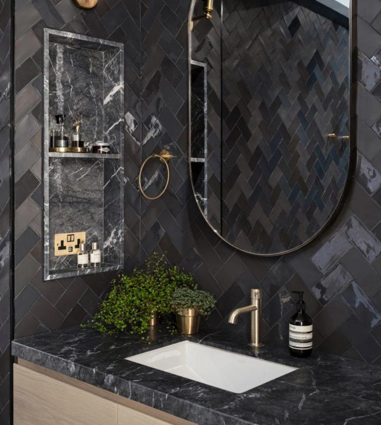 Vous pouvez voir du marbre noir élégant, des carreaux brillants et de l'or et du laiton chic