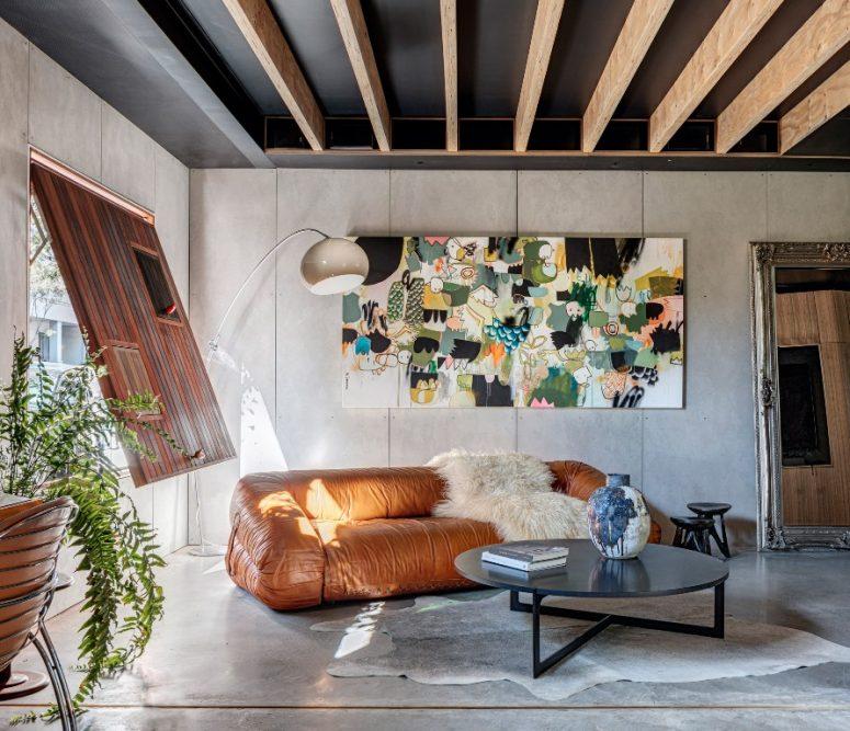 Le salon présente une œuvre d'art unique, un canapé en cuir et un volet en bois avec mini-fenêtres