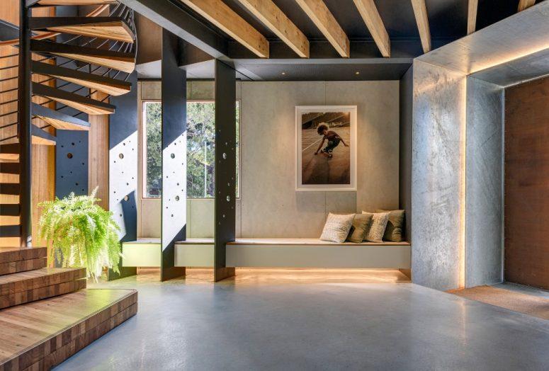 L'entrée est vaste, avec des panneaux perforés créatifs, un grand escalier et un banc intégré éclairé