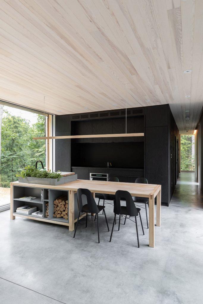 La cuisine est faite en noir, il y a un îlot de cuisine en bois et en pierre qui se double d'une table à manger