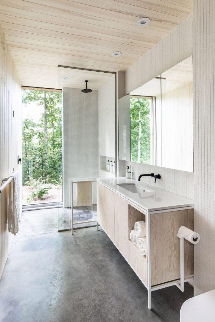 La salle de bain est entièrement neutre, avec des carreaux blancs et du contreplaqué neutre et une vue magnifique sur la forêt