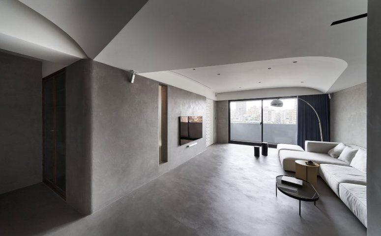 Le salon est fait avec un grand sectionnel, une télévision, un lampadaire et des souches d'arbres