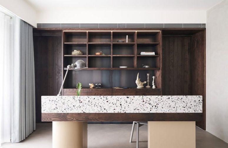 Le bureau à domicile est également là, avec un grand meuble de rangement teinté sombre, un bureau sombre avec du terrazzo