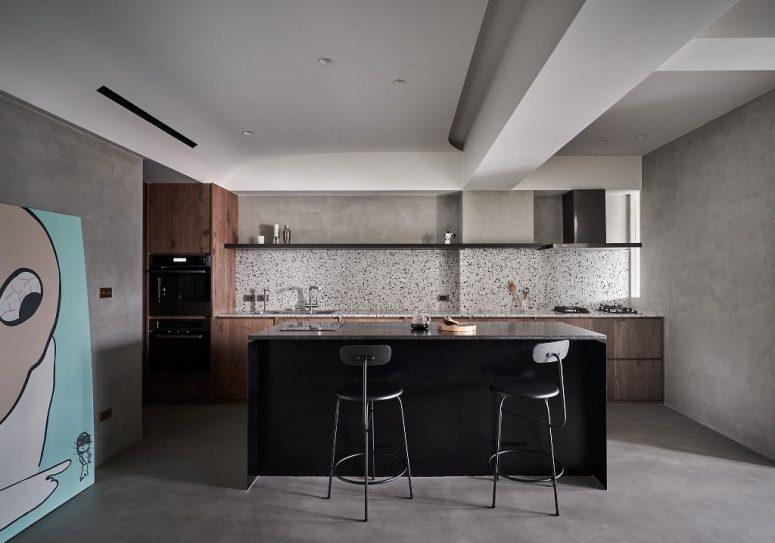 La cuisine est faite avec des armoires en bois teinté, un îlot de cuisine noir et un dosseret en terrazzo frais
