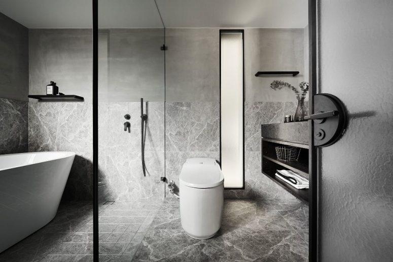 La salle de bain est faite en gris, avec des appareils blancs et des touches noires