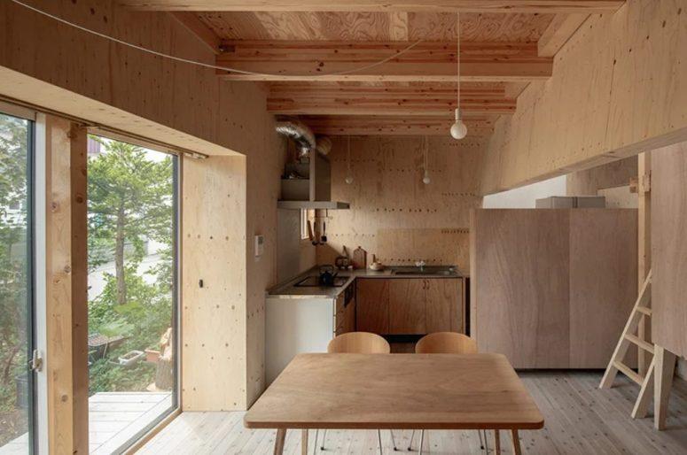La cuisine et l'espace salle à manger sont réunis en un seul, avec des meubles simples en bois et en contreplaqué, des ampoules suspendues et un mur vitré avec une entrée dans la cour