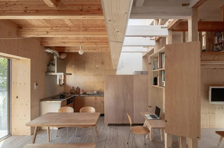 Une grande unité de rangement avec un bureau caché divise les espaces repas et le salon, et les puits de lumière leur donnent une sensation de fraîcheur