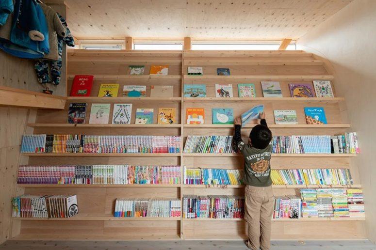 Un mur incurvé avec beaucoup de livres a inspiré l'enfant à lire