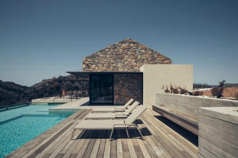 Il y a une grande terrasse avec des chaises longues devant la piscine
