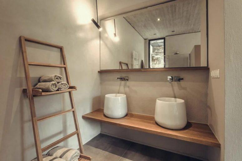 La salle de bain comprend une vanité flottante, deux lavabos accrocheurs et des étagères