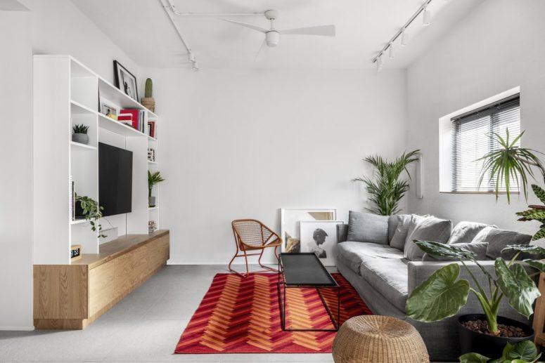 Le salon est très confortable, avec un tapis lumineux pour un accent, des plantes en pot et du chêne