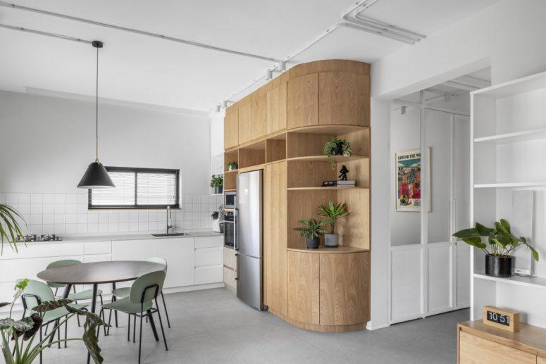 La cuisine, la salle à manger et le salon sont combinés dans un grand espace ouvert avec un sol gris clair, des murs blancs et des accents de meubles en chêne