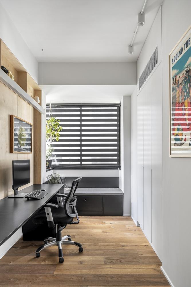 Le bureau à domicile est petit et laconique, avec un long bureau, assez pour deux, un banc de fenêtre et de la verdure