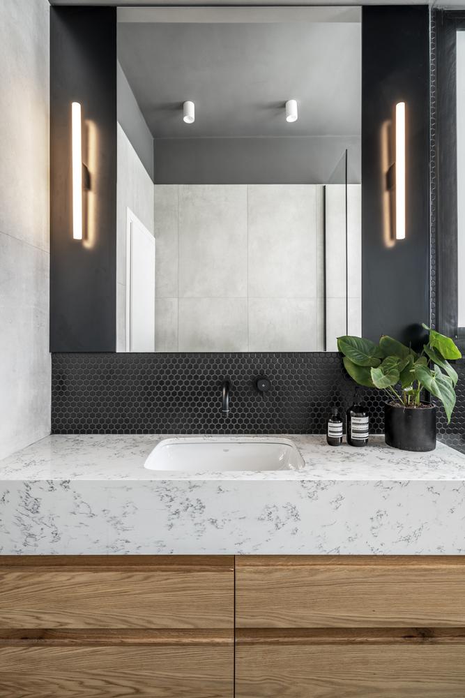 Le marbre blanc complète le bois et les carreaux de mur et de sol sombres, établissant l'harmonie ici
