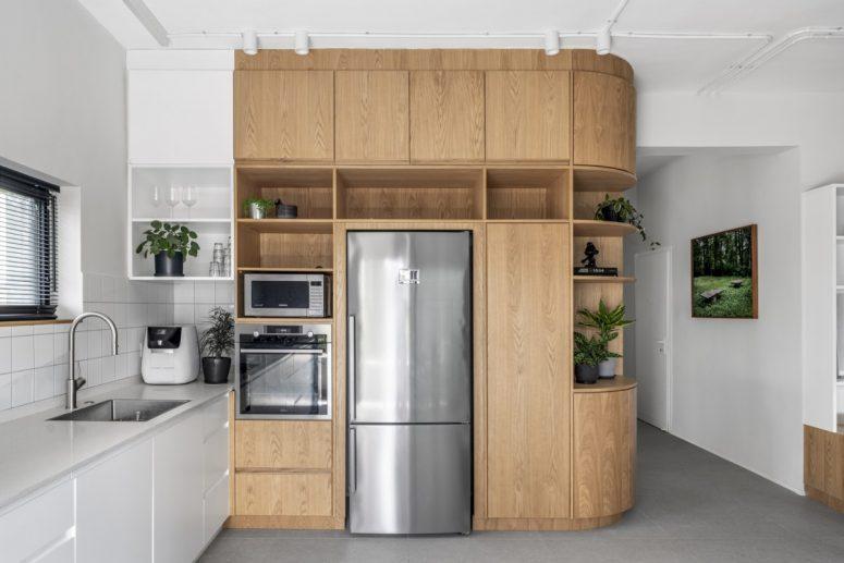 La cuisine a une belle unité en chêne personnalisée avec une extrémité incurvée et un design élégant et moderne