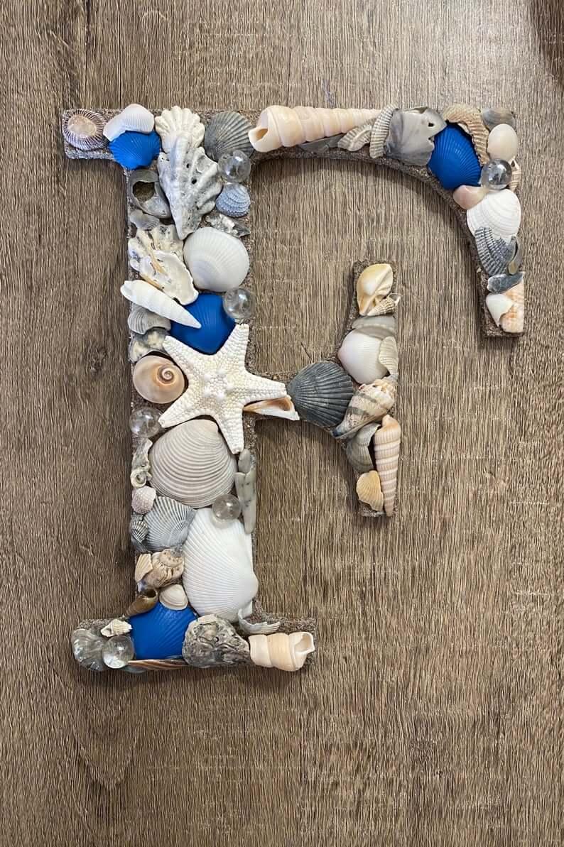 Initiale décorée de coquillage beige et bleu