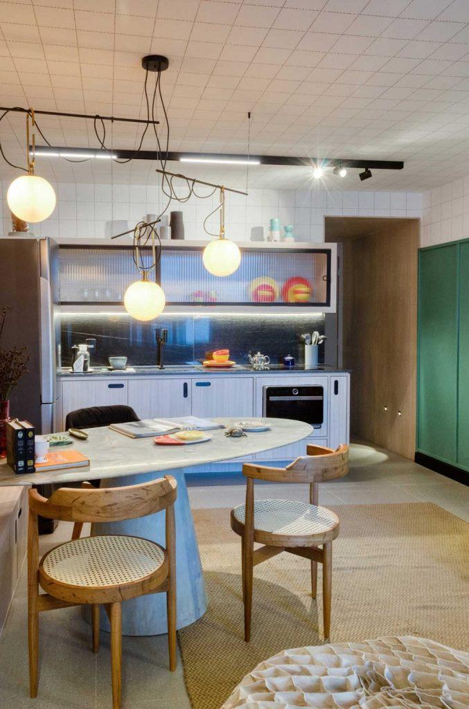 Le plafond est recouvert de carreaux blancs, il y a des lampes modernes suspendues au-dessus de la table et des chaises en osier