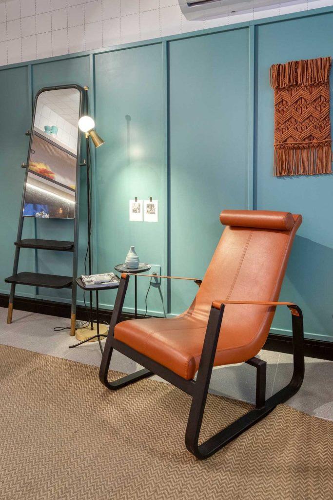 Ce coin lecture présente une chaise orange et une suspension en macramé boho ainsi que des tables d'appoint