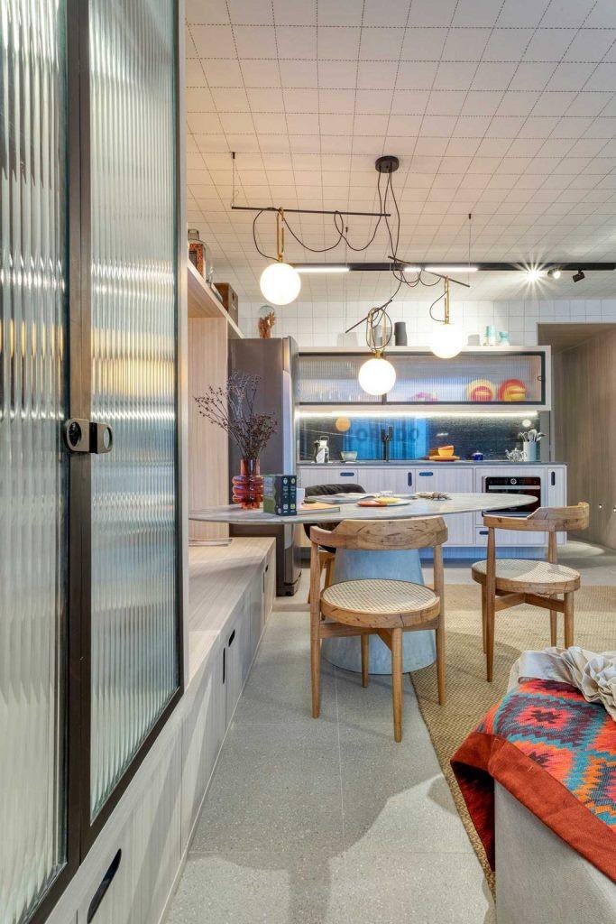 La cuisine est de couleur claire, avec un dosseret en marbre noir, la table en marbre se tient à côté d'un grand meuble de rangement qui se double d'un banc