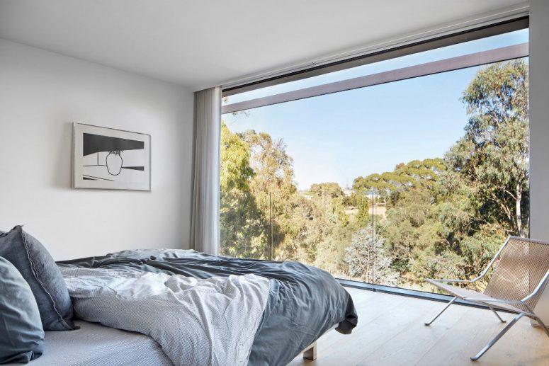 La chambre principale dispose d'un mur de verre avec vue et mobilier minimaliste