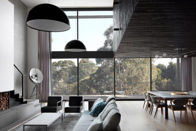 La disposition principale est un salon, une salle à manger et une cuisine avec des murs vitrés et une cheminée