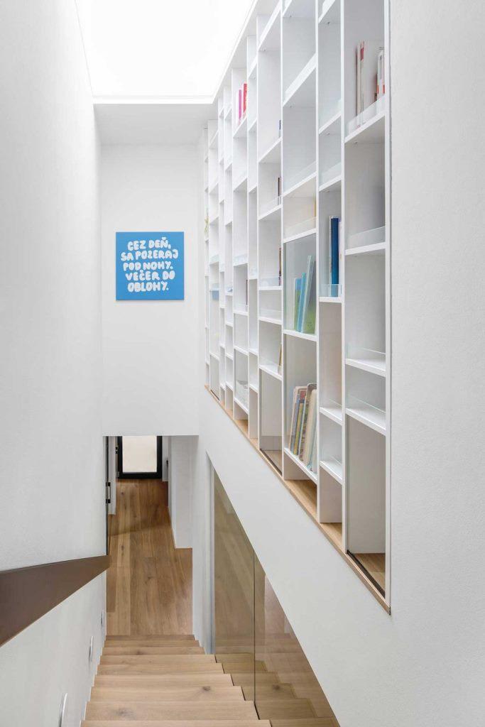Une étagère géante est placée au-dessus des escaliers pour utiliser également cet espace peu commode