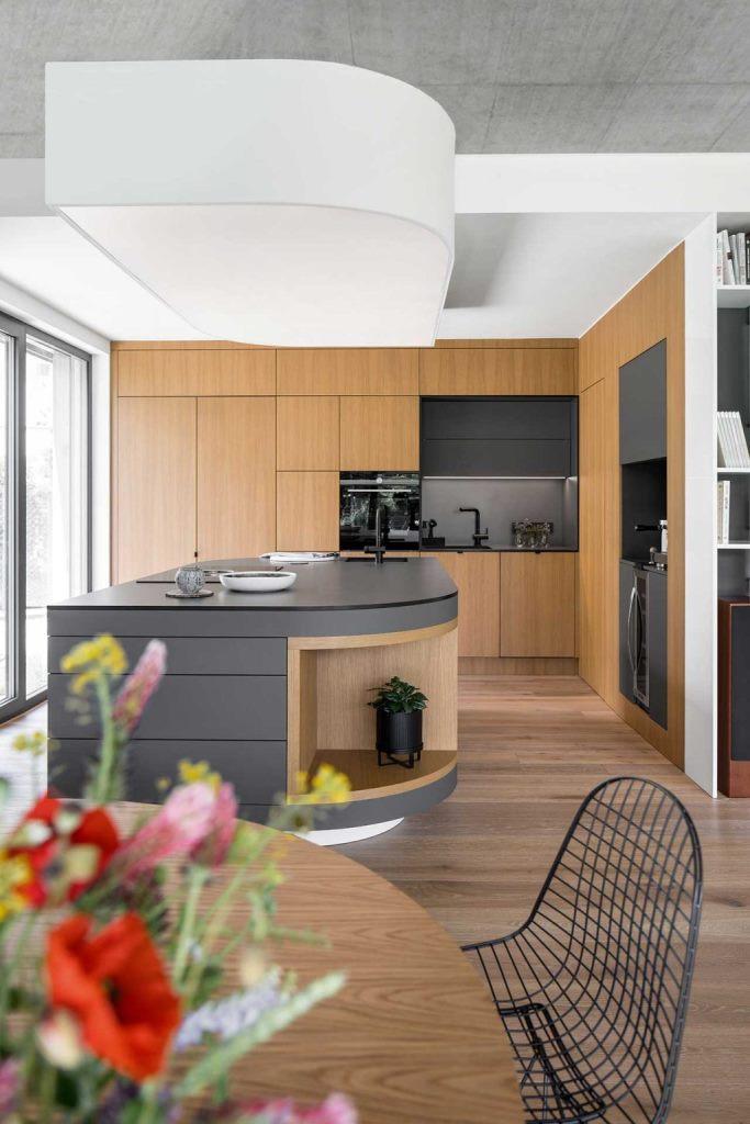 La cuisine est faite avec des armoires et des surfaces élégantes, avec un plateau en béton et un dosseret