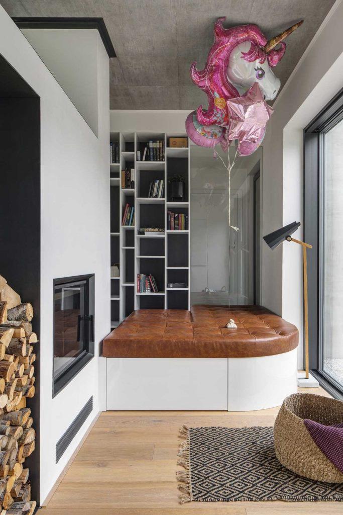 Il y a un coin lecture confortable avec un siège et un rangement en cuir, et les vues sont disponibles à travers un mur de verre