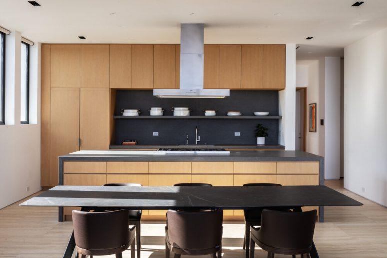 La cuisine est minimaliste, avec des armoires neutres élégantes, un dosseret sombre et un espace salle à manger laconique avec une table en marbre