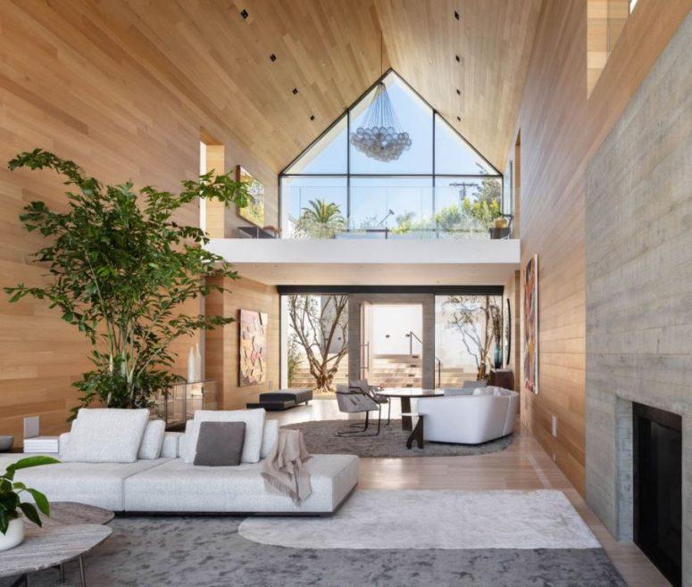 Le salon a un plafond à double hauteur et l'espace est très ouvert, avec beaucoup de meubles légers et élégants