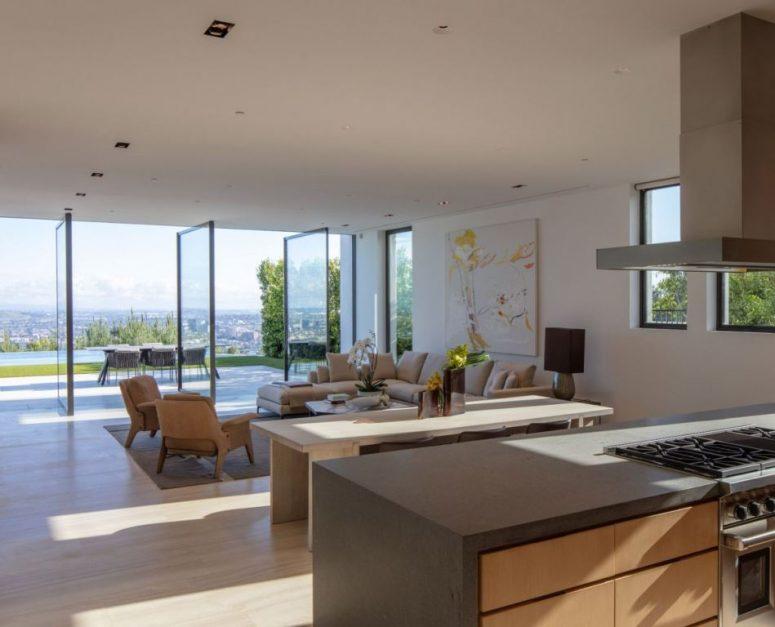 Le salon est fait avec des portes pivotantes en verre qui aident l'espace à fusionner avec l'extérieur