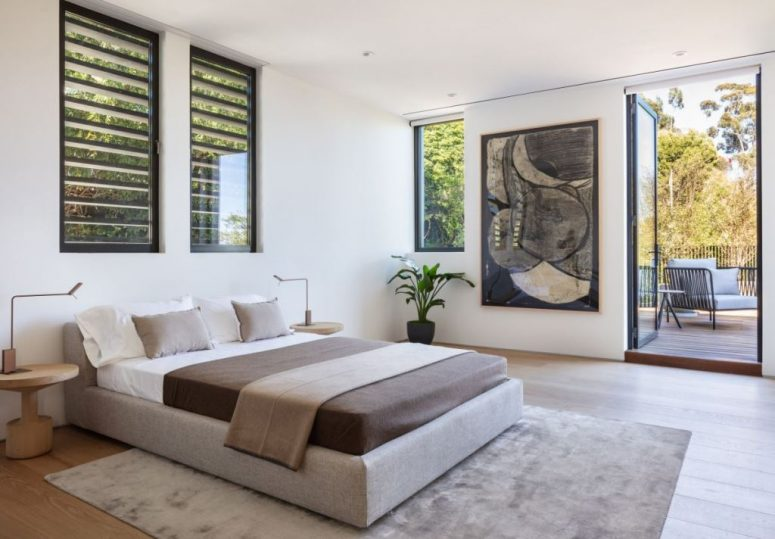 La chambre est faite dans une palette de couleurs neutres, avec une œuvre d'art et il y a un accès à l'extérieur