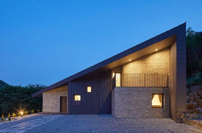 La maison présente des panneaux métalliques et de la brique à l'extérieur et un aménagement paysager qui correspond à la maison