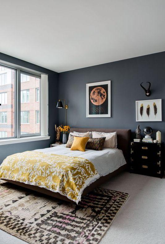 une chambre chic avec des murs gris graphite, un lit marron, des tables de nuit dépareillées, des draps jaunes et des textiles imprimés