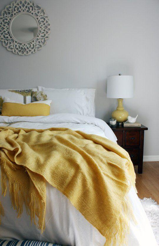 une chambre chic avec des murs gris tourterelle, des draps blancs et jaunes ensoleillés, une lampe moutarde et des touches chics