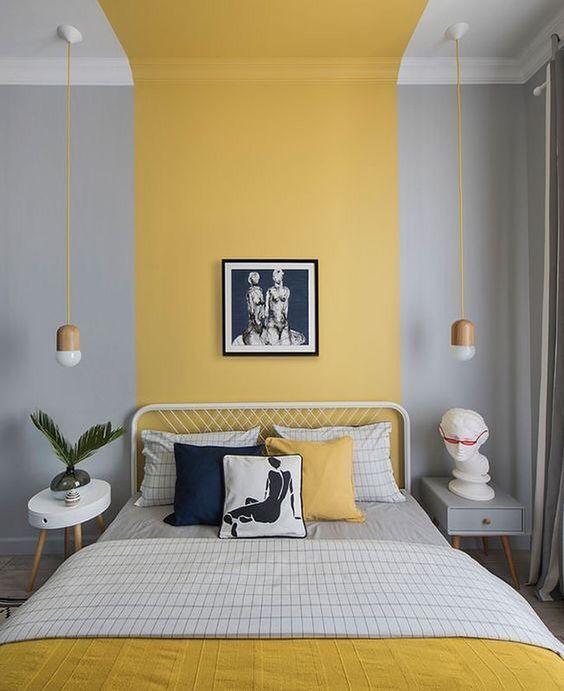 une chambre contemporaine avec des murs en blocs de couleur gris tourterelle et jaune, des meubles blancs et gris, une literie grise et jaune et des suspensions