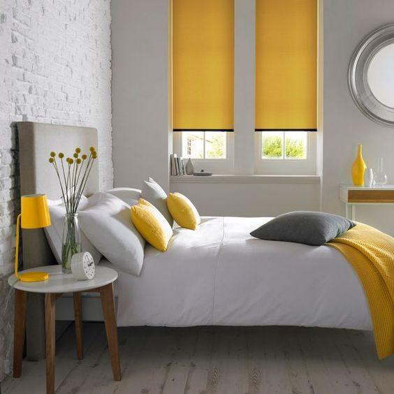 une chambre minimaliste grise et jaune avec des meubles simples et minimalistes, un lit gris, des draps jaunes et des textiles neutres