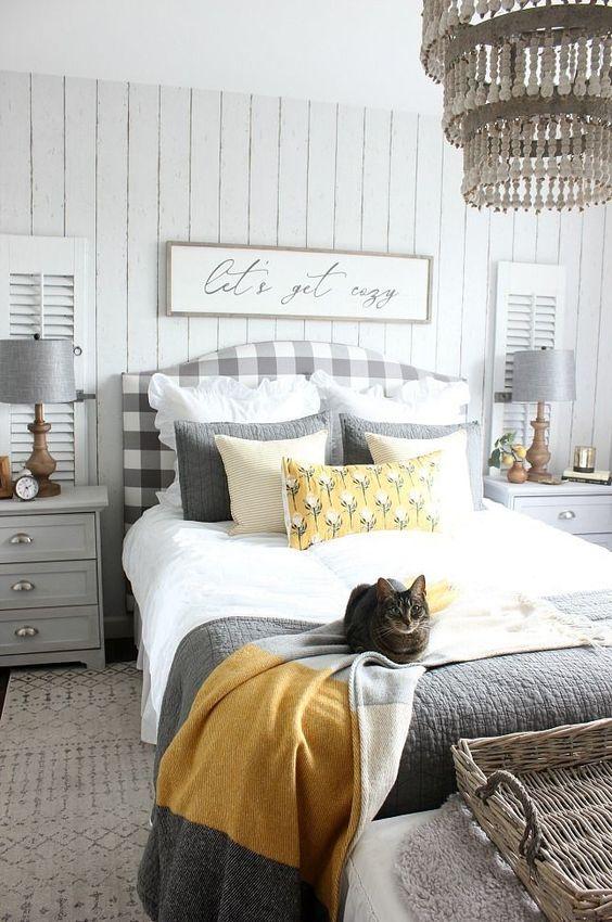 une chambre de ferme confortable avec un lit à carreaux gris, des tables de chevet et des lampes gris tourterelle, une literie grise et jaune