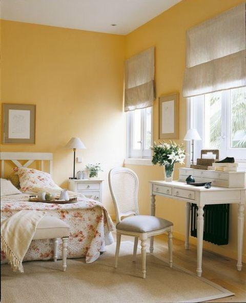 une chambre romantique jaune ensoleillée avec des meubles blancs vintage raffinés, des textiles gris tourterelle et une literie fleurie