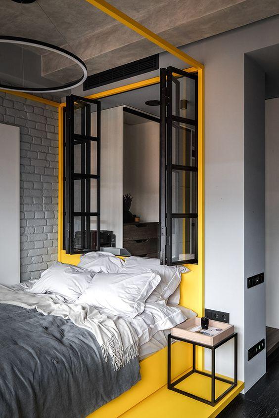 une chambre industrielle moderne avec des murs gris clair, un mur de briques grises, une zone jaune avec une fenêtre et un lit jaune avec une literie grise