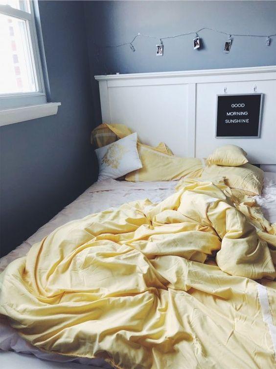 une chambre moderne gris graphite avec un lit blanc, des lumières et des photos et une literie jaune citron pour embellir l'espace