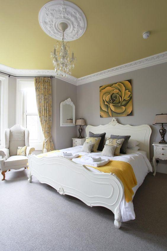 une chambre raffinée avec des murs gris tourterelle, un plafond jaune pâle, un élégant mobilier crémeux, un lustre en cristal et des touches de moutarde