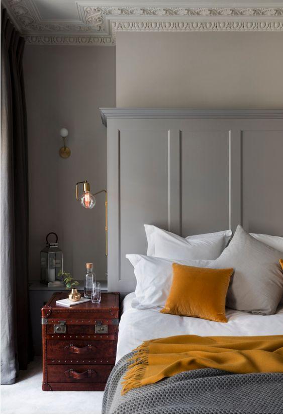 une chambre raffinée avec des murs gris tourterelle, des moulures, une commode vintage comme table de chevet, des draps moutarde et des touches d'or