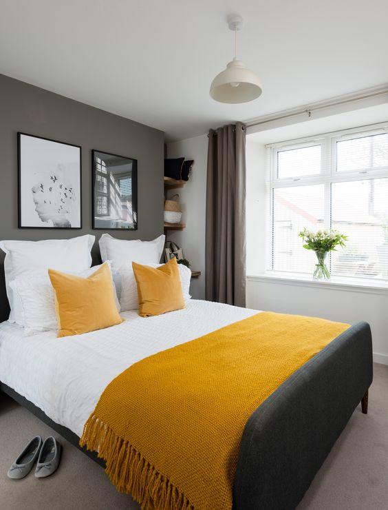 une chambre contemporaine élégante avec des murs et un sol gris, un lit gris graphite, des draps moutarde et des rideaux taupe