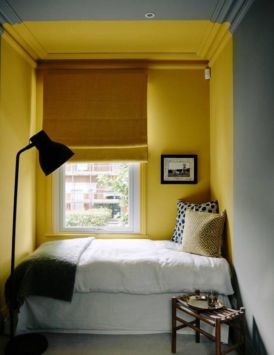une petite chambre confortable avec des murs gris et un coin jaune soleil avec un lit, un rideau moutarde et une literie grise et jaune