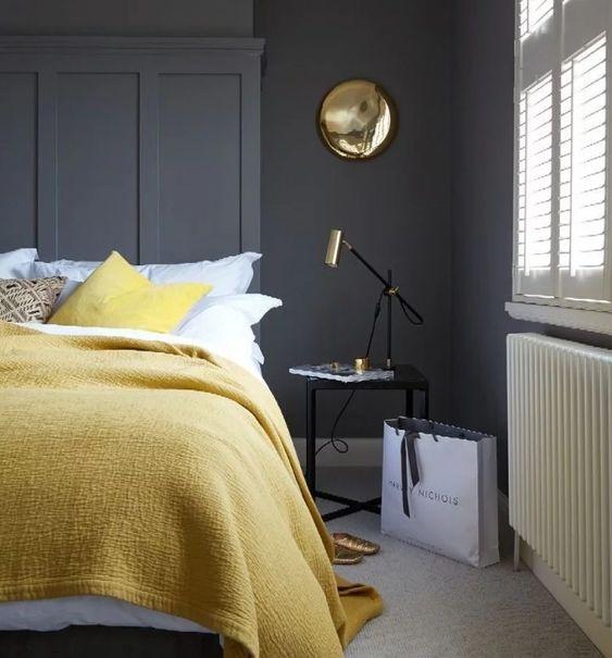 une chambre élégante avec des murs gris graphite, des meubles simples et élégants, des textiles jaune citron et des touches dorées
